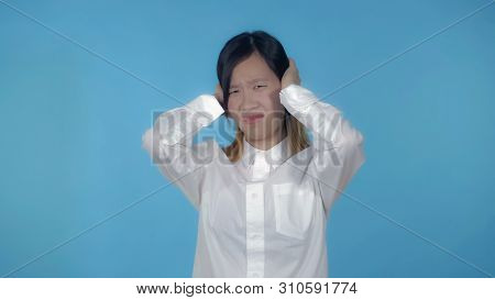 Young Asian Woman Posing Showing Hand Gesture Loud Sound On Blue Background In Studio. Attractive Mi