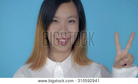 Close Up Portrait Young Asian Woman Shows Sign Symbol Victory On Blue Background In Studio. Attracti