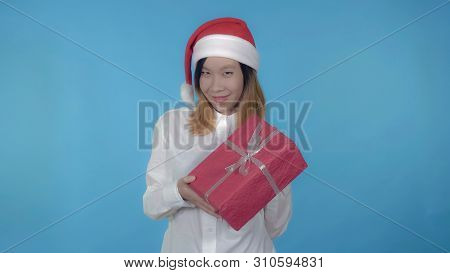 Young Asian Woman Posing Wearing Santa Claus Hat Showing Red Box With Present On Blue Background In