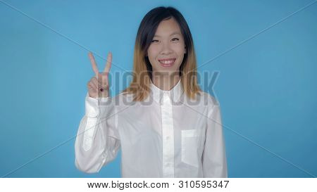 Young Asian Woman Posing Showing Hand Gesture Victory On Blue Background In Studio. Attractive Mille