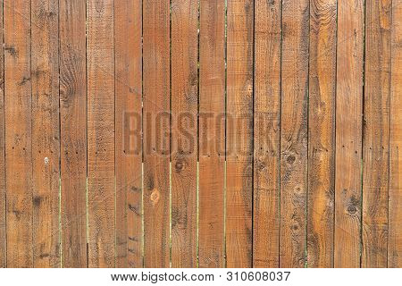 Pattern Of Stained, Reddish Brown Wood Slats Of A Privacy Fence That Show Signs Of Fading And Stains
