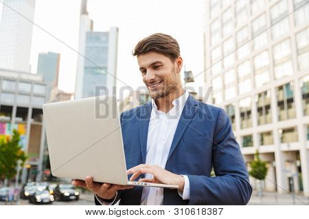 Picture of a smiling happy handsome young business man standing near business center using laptop computer.