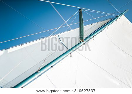 White Cloth Fabric, Masts And Ropes Close-up On The Sail Of Tri-yacht Or Yacht Sailing Boat