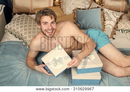 Opening His Present. Handsome Guy With Box On Birthday Morning. Sexy Man Smiling With Birthday Gift