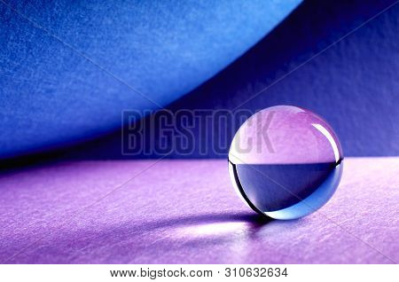 Crystal Ball On Blue And Pink Background. Glass Ball With Shades And Reflections