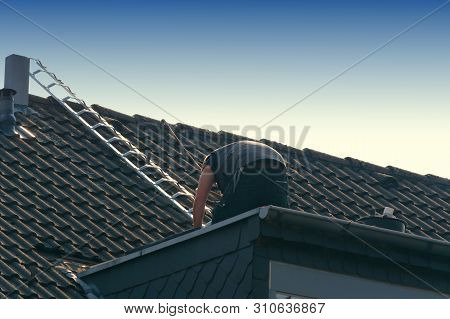 Roofer Works On An Unfinished Roof. Installs Roof Shingles