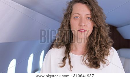 Businesswoman portrait in private jet. Well dressed, confident female caucasian entrepreneur smiling inside of business airplane cabin.