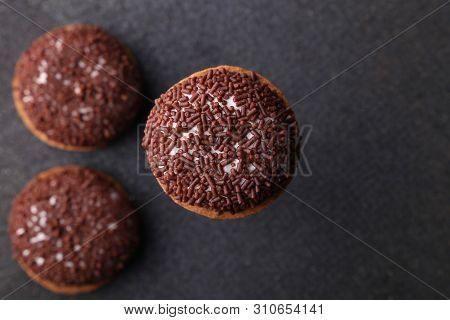 Chocolate Crinkle cookies. close-up of Crinkle cookies chocolate biscuits on Christmas cookies on a black plate, view from above. poster