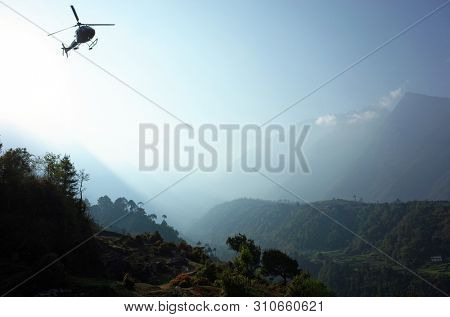 Helicopter flying over green Himalaya mountains from Tenzing–Hillary Airport in Lukla, Nepal