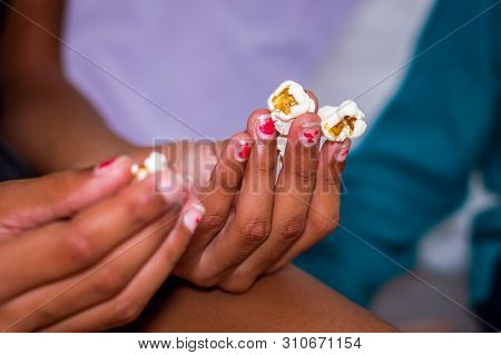 Close Up Hands Of Little Black Girl Holding Popcorns While Watching Movie At Home.