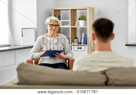 psychology, mental therapy and people concept - senior woman psychologist with clipboard and young man patient at psychotherapy session