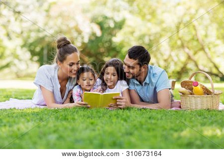 family, leisure and people concept - happy mother, father and two daughters laying on picnic blanket and reading book in summer park