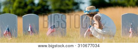 panoramic shot of kid in dress and straw hat sitting near headstone with american flag in graveyard poster