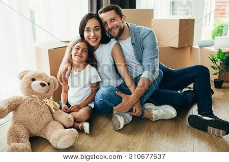 Happy Family Hugging Sitting On The Floor Into Their New House. It Is Wonderful Moving To A New Apar