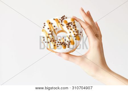 Female Hand Holding Delicious Donut With White Glaze, Caramel And Chocolate Sprinkles. Party Concept