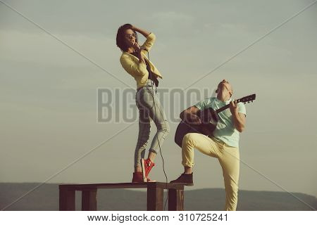Musician. Woman, Singer Or Girl Singing On Table And Handsome Man, Guitarist Playing Acoustic Guitar