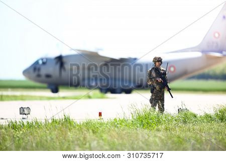 Boboc, Romania - May 22, 2019: Romanian Army Soldier Patrols A Military Air Base, With An Alenia C-2