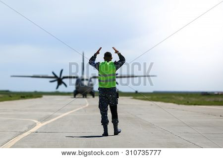 Boboc, Romania - May 22, 2019: Ground Personnel Is Aircraft Marshalling An Alenia C-27j Spartan Mili