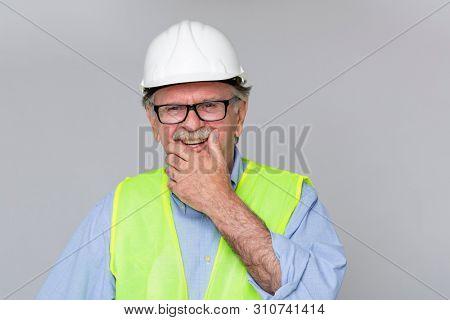 Smiling elderly mustache man with white construction helmet