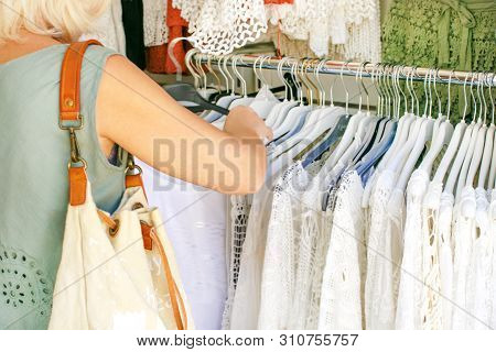 Caucasian Woman Selecting Dress In A Clothes Shop. Woman Choosing Dress During Shopping At Garments