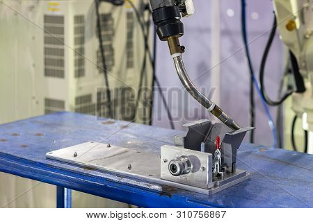 close up workpieces setting on jig fixture with manual quick clamp and torch of electric mig robot welding process at factory poster