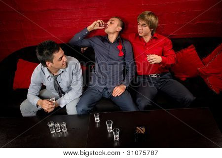 Men drinking shots in night club