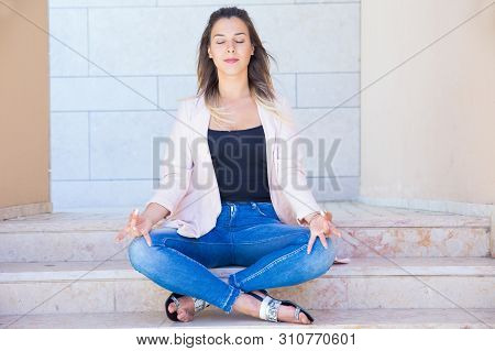 Peaceful Tranquil Young Woman Meditating Near City Building. Serene Beautiful Woman Sitting On Stair