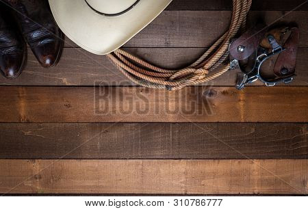 American Cowboy Items incluing a lasso spurs and a traditional straw hat on a wood plank background