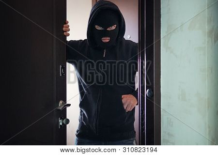 Evil threat to Rob broke into private ownership. Breaking into an apartment. Maniac went into the house. The concept of crime and violence. Open door to a stranger. A gun or a knife in your pocket poster