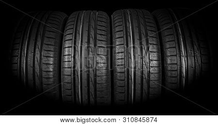 Studio Shot Of A Set Of Summer Car Tires On Black Background. Tire Stack Background. Car Tyre Protec