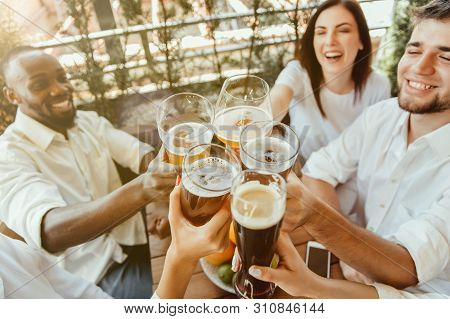 Young Group Of Friends Drinking Beer, Having Fun, Laughting And Celebrating Together. Women And Men