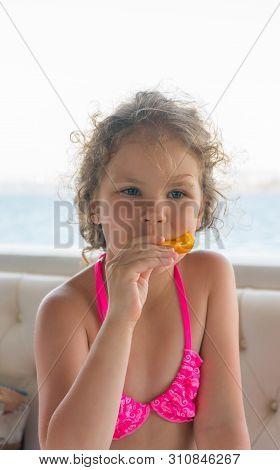 Baby With Orange. Happy Little Girl Eating Orange Near The Sea.