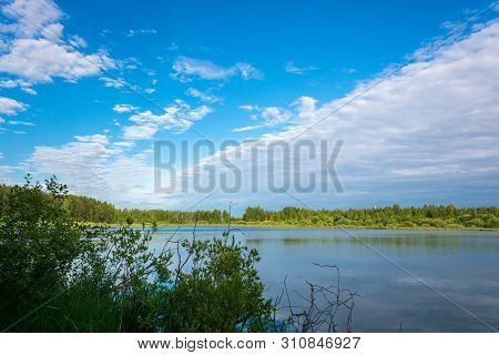 A Small Lake On Overgrown Shores And A Beautiful Cloudy Sky.