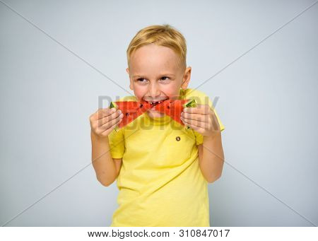 Frolicsome Caucasian 5 Year Old Boy Without Incisor Capering And Eating Pieces Of Red Watermelon, De