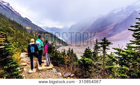 Senior Man And Women Hiking On The Moraines Of The Victoria Glacier From The Plain Of Six Glaciers T