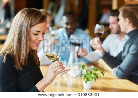 Young woman is drinking a glass of wine on a wine tasting together with friends