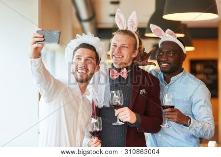 Friends make selfie at bachelor party in a bar as a reminder