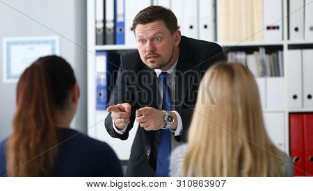 Portrait Of Serious Businessman Looking At Brunette With Indignantly. Angry Male Manager Pointing At