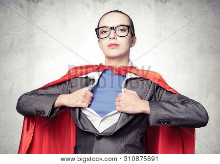 Attractive Young Business Lady In Red Hero Cape On Grey Wall Background. Portrait Of Business Woman