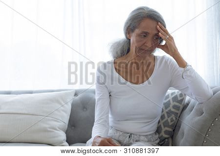 Front view of senior mixed race woman sitting on couch at home. Authentic Senior Retired Life Concept