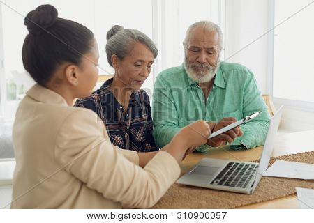 Side view of financial adviser discussing information with a African-American couple indoor. Authentic Senior Retired Life Concept