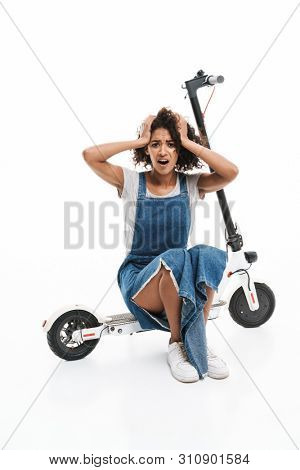 Image of perplexed african american woman grabbing head while sitting on electronic scooter isolated over white background poster