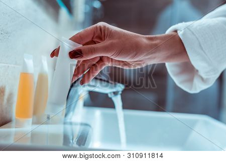 Woman With Accurate Nail Taking Container With Face Wash
