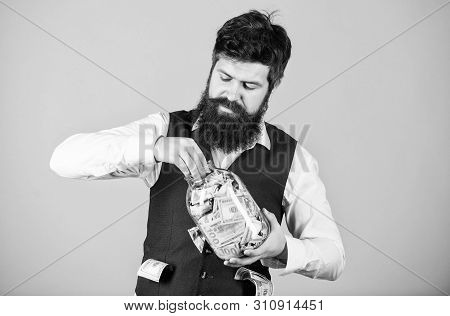 poster of Making an investment. Businessman taking cash money out of glass jar for investing activities. Bearded man investing money into startup business. Investing for future benefit. Investing capitalist
