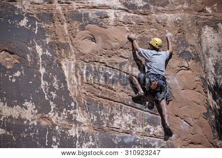 Rock climber man  free climbing solo up handholds and footholds on red sandstone cliffs to set pitons and ropes in Moab, Utah, USA, May 7, 2019