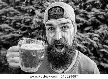 Man relaxing enjoying beer hot summer day. Beer and ale concept. Quench thirst. Alcohol drink and bar. Hipster brutal bearded man hold mug cold fresh beer. Craft beer is young, urban and fashionable poster