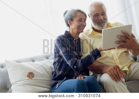 Side view of African-American couple sitting on a couch while using digital tablet. Authentic Senior Retired Life Concept