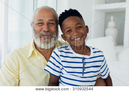 Portrait close up of African-American boy and mixed race man smiling inside a room. Authentic Senior Retired Life Concept