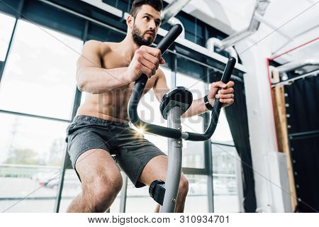 handsome bearded sportsman training on elliptical machine at gym poster