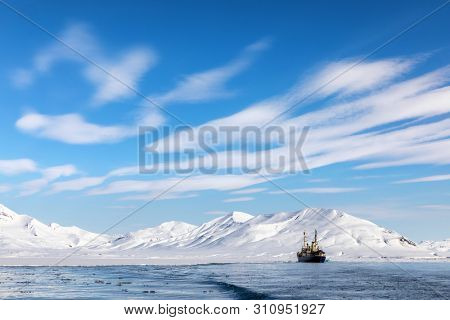 Boat on the fjords of Svalbard, a Norwegian archipelago between mainland Norway and the North Pole, with snowy mountains and blue sky.